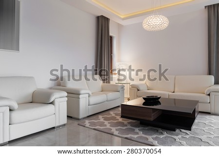 Contemporary cozy family room with three comfortable sofas - stock photo