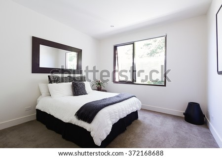 Contemporary decor in black and white themed show home bedroom interior - stock photo