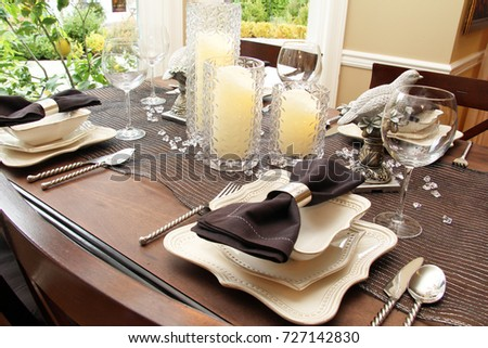 Contemporary dining room table set for Christmas or Thanksgiving dinner.