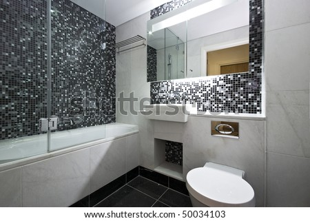 Contemporary en-suite bathroom in black and white with white ceramic bath tub, wash basin and toilet with mosaic tiled walls and marble fragments
