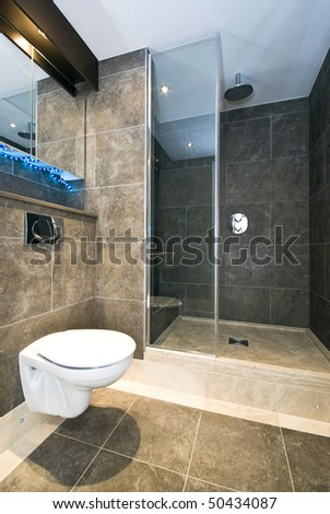 Contemporary en-suite bathroom with natural stone tiles and marble fragments in cappuccino brown - stock photo