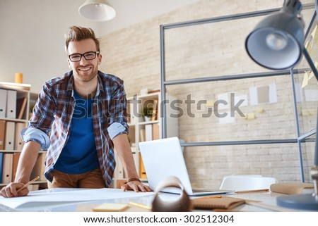 Contemporary engineer looking at camera during work in office - stock photo
