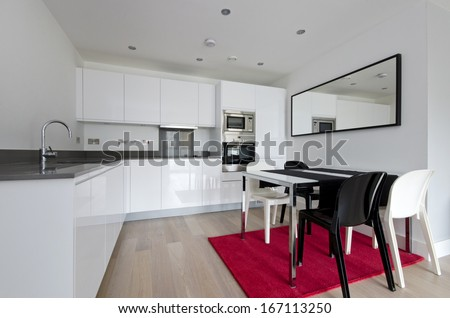 Contemporary fully fitted kitchen with white units, modern chrome finish appliances, modern dining table and designer chairs - stock photo