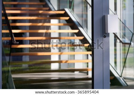 Contemporary hardwood staircase behind a glass door - stock photo
