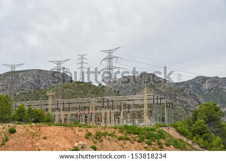 Contemporary high voltage power plant in mountains - stock photo