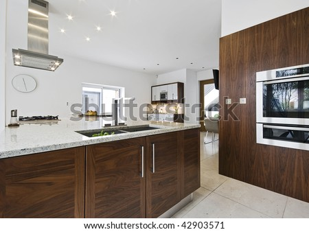 contemporary luxury kitchen with working isle and granite worktop - stock photo