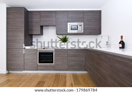 Contemporary modern fully fitted kitchen in brown with top spec appliances and granite worktops - stock photo