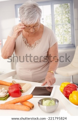 Contemporary old lady using tablet in kitchen to prepare healthy meal. - stock photo
