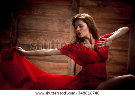 Contemporary pretty ballerina posing and jumping over wooden background. Sexy long-haired woman performing in red dress.