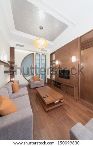 Contemporary room with a sofa, an armchair and a wooden table in the center - stock photo