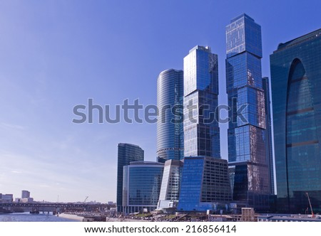 Contemporary russian architecture concept: modern, futuristic skyscrapers and city office buildings in Moscow (Russia) with reflections in glass wall windows with a blue sky and clouds as a background - stock photo
