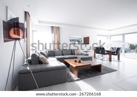 Contemporary sitting room with gray corner sofa - stock photo