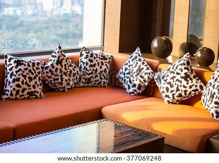 contemporary sofa and pillows near windows warm lighting - stock photo