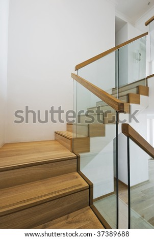 contemporary stair case with wooden steps and glass rails - stock photo