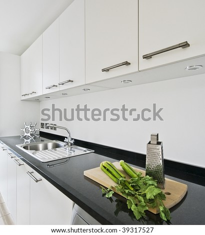 contemporary white kitchen with black granite worktop - stock photo