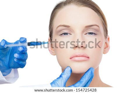 Content attractive model on white background having an injection on the cheek