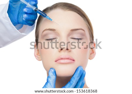 Content attractive model on white background having botox injection on the forehead - stock photo