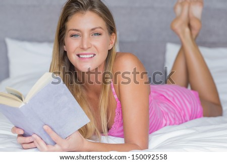 Content blonde lying on her bed reading a book at home in bedroom