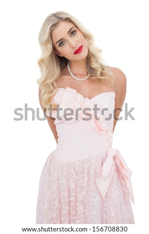 Content blonde model in pink dress posing looking at camera on white background - stock photo