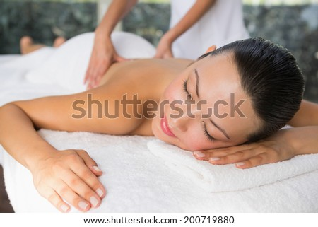 Content brunette enjoying a back massage at the health spa - stock photo