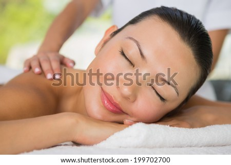 Content brunette getting a back massage at the spa