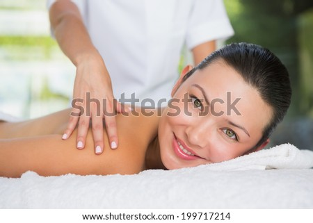 Content brunette getting a back massage smiling at camera at the spa - stock photo