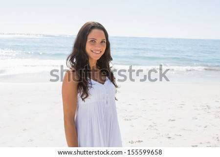 Content brunette in white sun dress looking at camera on the beach