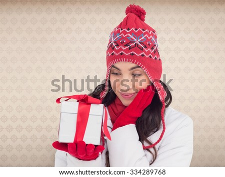 Content brunette in winter clothes holding gift against room with wooden floor