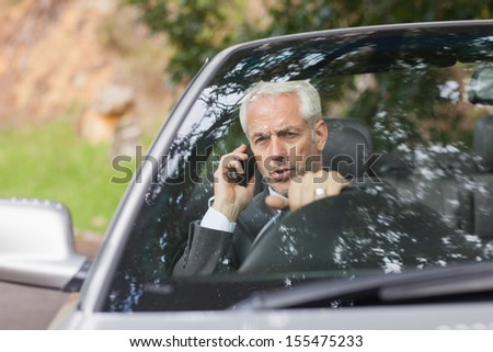 Content businessman on the phone driving expensive cabriolet on sunny day