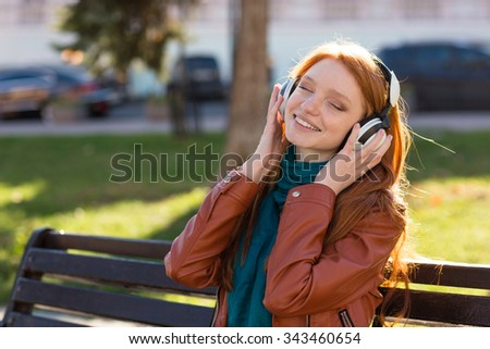 Content cheerful young woman in leather jacket and scarf sitting on bench in park and listening to music with eyes closed - stock photo