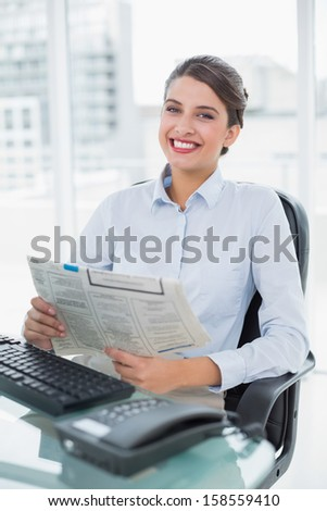 Content classy brown haired businesswoman reading a newspaper in bright office - stock photo