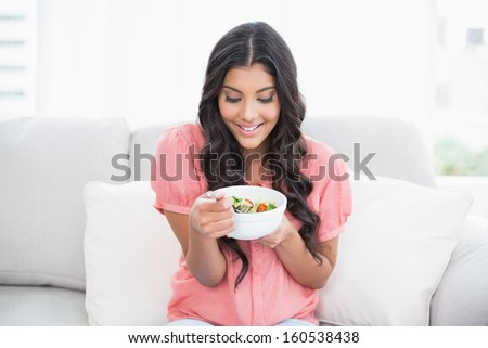 Content cute brunette sitting on couch holding salad bowl in bright living room - stock photo