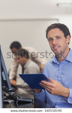 Content male student holding his tablet sitting in computer class smiling at camera - stock photo
