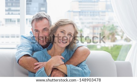 Content man hugging his wife on the couch smiling at camera at home in the living room - stock photo