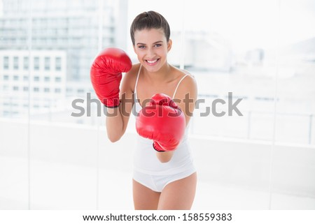 Content natural brown haired woman in white sportswear wearing boxing gloves in bright living room