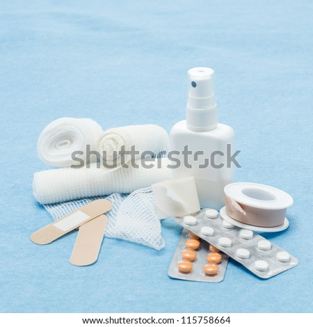 Content of First aid kit plasters, bandage and pills - stock photo