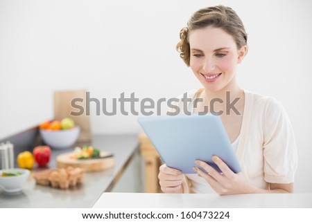 Content peaceful woman using her tablet sitting in her kitchen at home