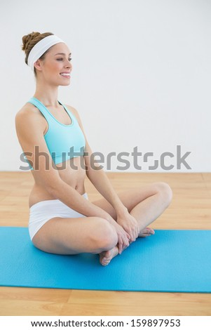 Content peaceful woman wearing sportswear sitting on blue exercise mat in sports hall