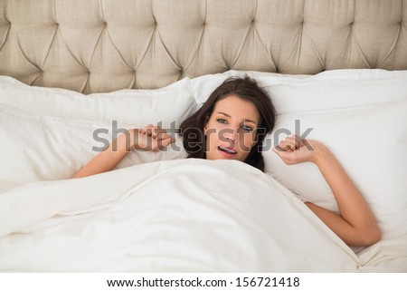 Content pretty brown haired woman waking up in a bright bedroom