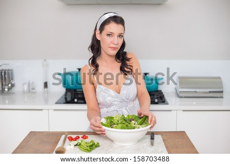 Content pretty brunette preparing healthy salad in bright kitchen - stock photo