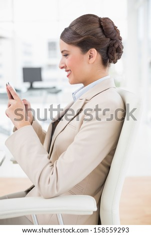 Content smart brown haired businesswoman using a mobile phone in bright office