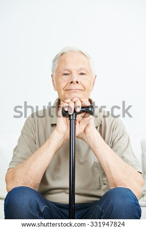 Content smiling old senior man with a cane in a nursing home