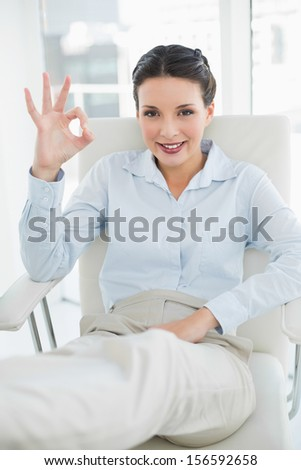 Content stylish brunette businesswoman making an okay gesture in bright office