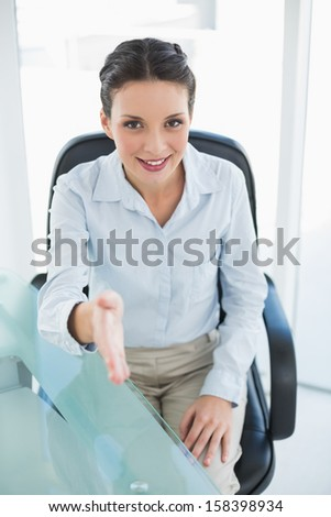 Content stylish brunette businesswoman presenting her hand in bright office