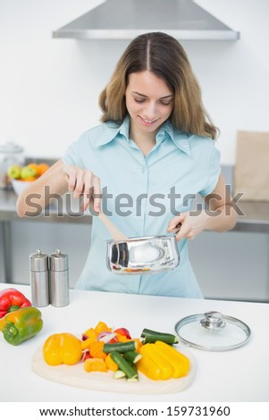Content woman cooking while standing in kitchen at home - stock photo