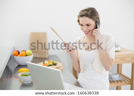 Content woman phoning with her smartphone in the kitchen looking at her laptop - stock photo