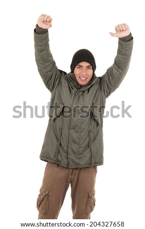 content young man wearing green winter coat and a beanie with arms up isolated on white - stock photo