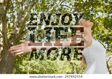 Content young woman doing yoga in a park against enjoy life more - stock photo
