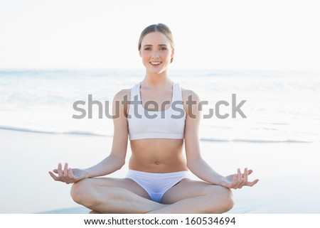 Content young woman sitting on the beach meditating smiling at camera - stock photo