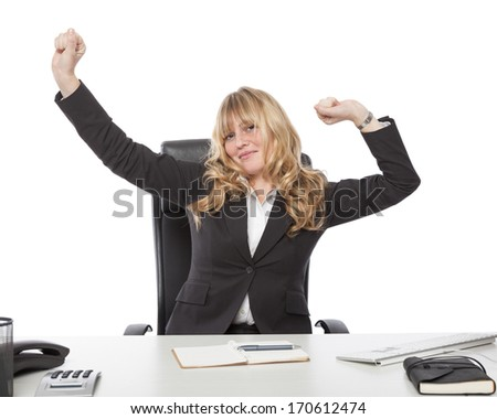 Contented beautiful young blond businesswoman stretching at her desk as she relaxes after completing her workload - stock photo